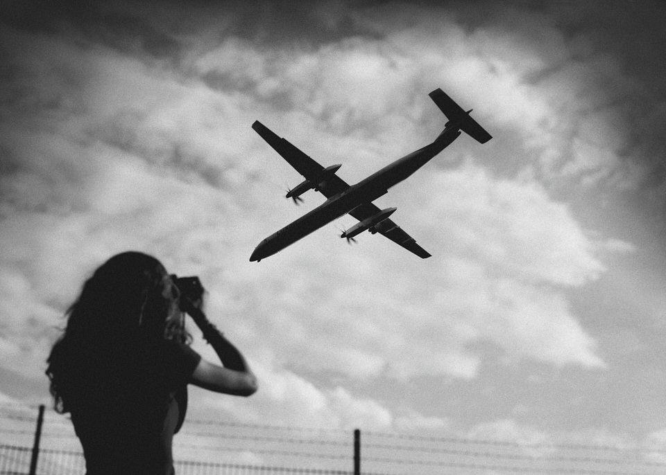 Eine Frau beobachtet ein Flugzeug