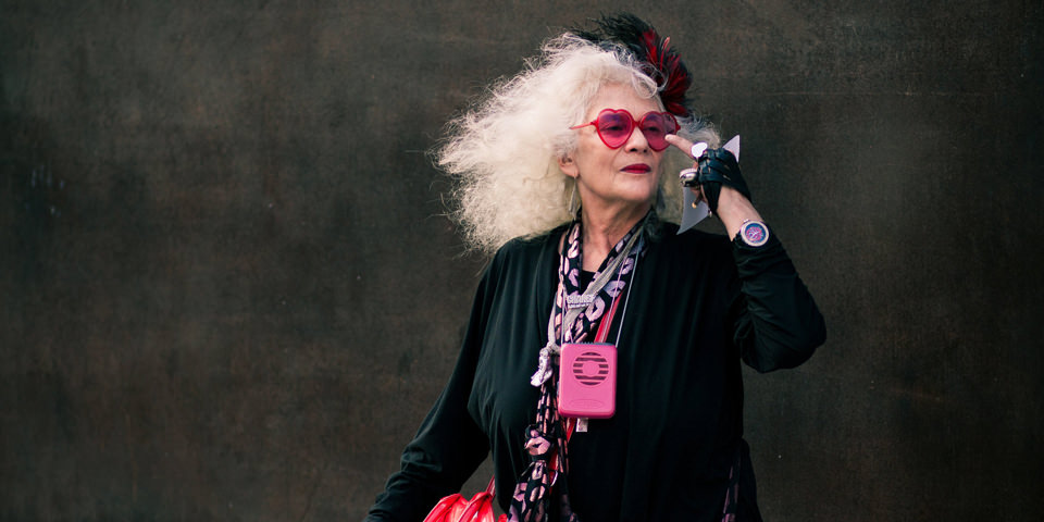 Eine Frau hält sich ihre rosa Brille mit dem Mittelfinger.