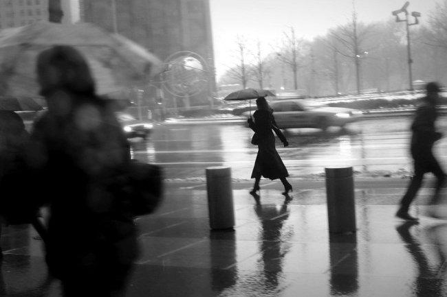 Eine Frau mit Schirm im Regen.