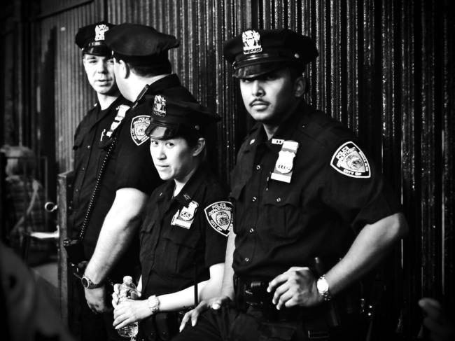 Vier Polizisten an einer Wand.