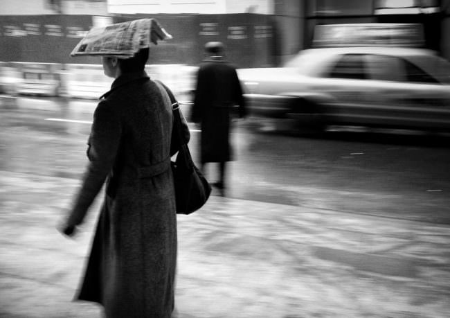 Eine Person schützt sich mit einer Zeitung auf dem Kopf vor dem Regen.