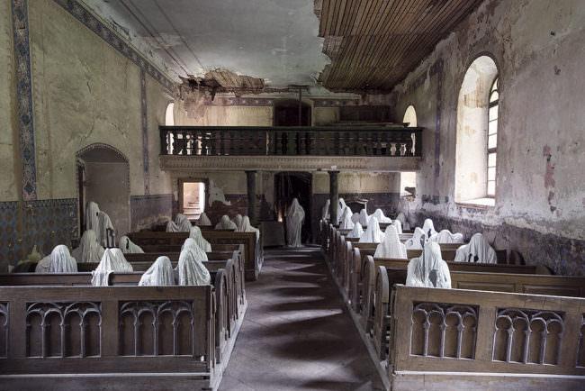Über 30 Geister aus Gips in einer Kirche sitzend.