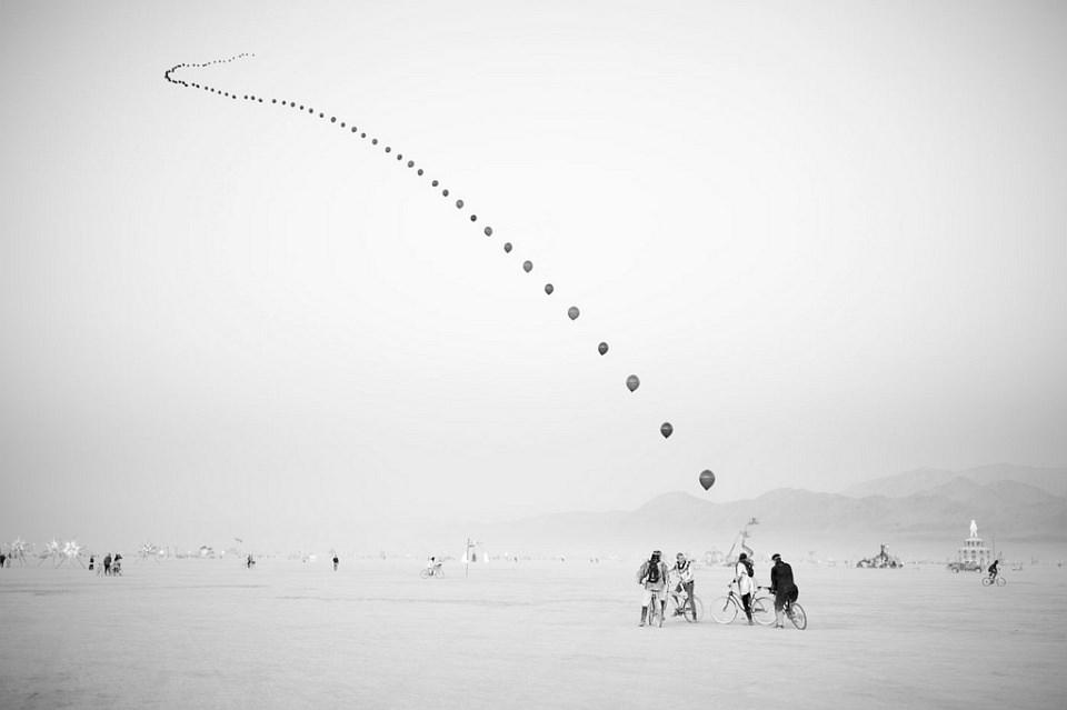 Aneinandergereihte Luftballons über der Wüste.