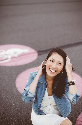 Eine Frau sitzt lachend auf der Straße.