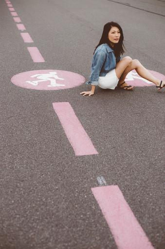 Eine Frau sitzt auf der Straße.