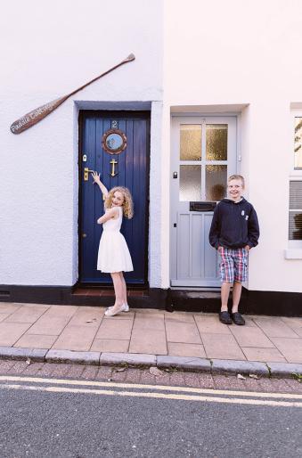 Zwei Kinder posieren vor einem Haus