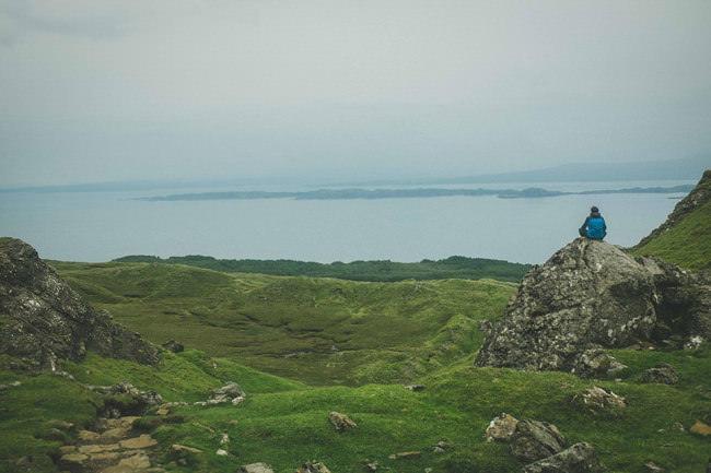 Eine Person sitzt in den schottischen Highlands