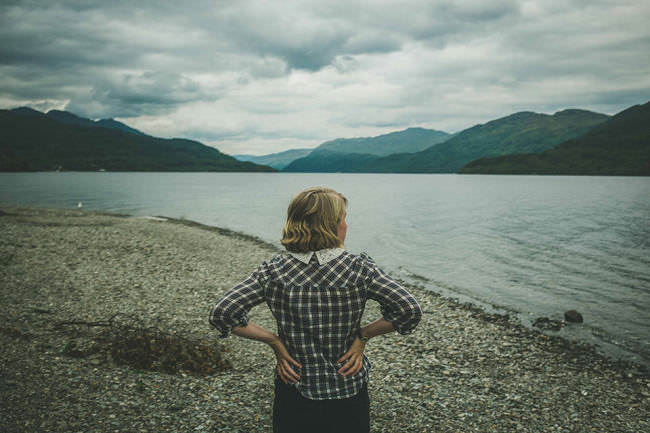 Eine Frau steht an einem See