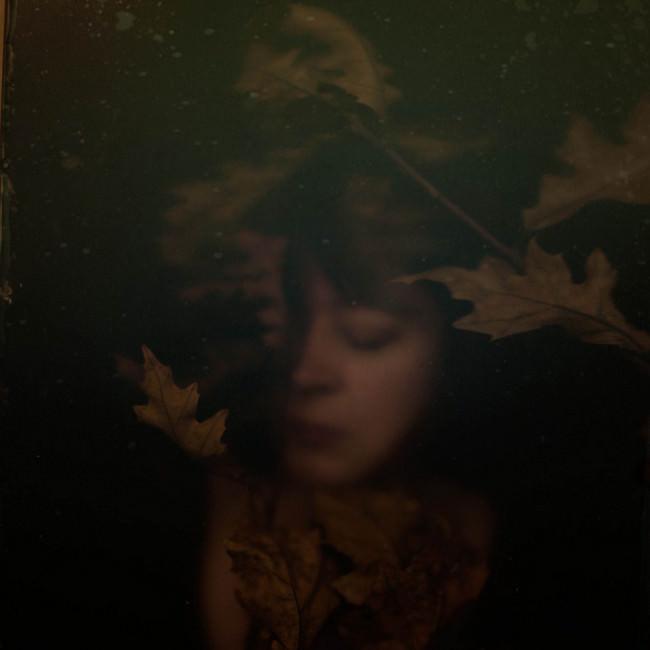Mädchen in dunklem Laub
