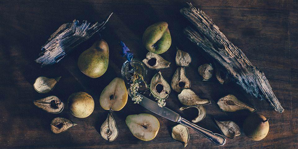 Birnen und Treibholz auf einem Tisch.