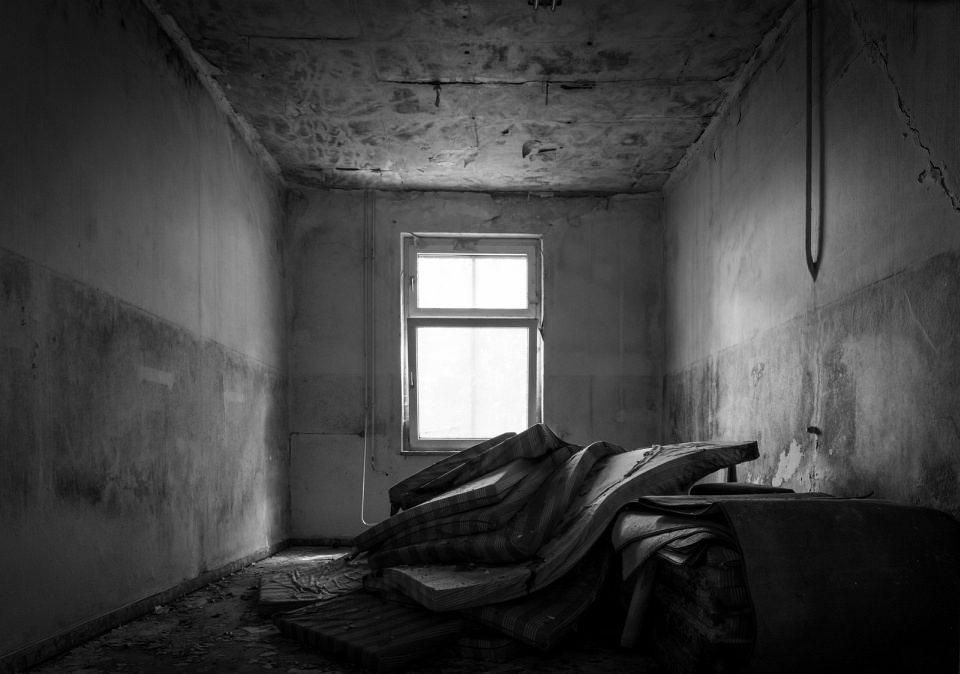 Stapel einiger Matratzen in einem verlassenen Raum; durch ein Fenster fällt Licht von hinten auf den Matratzenstapel.