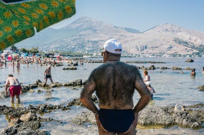 Ein stark behaarter Mensch steht am Stand in Palermo.