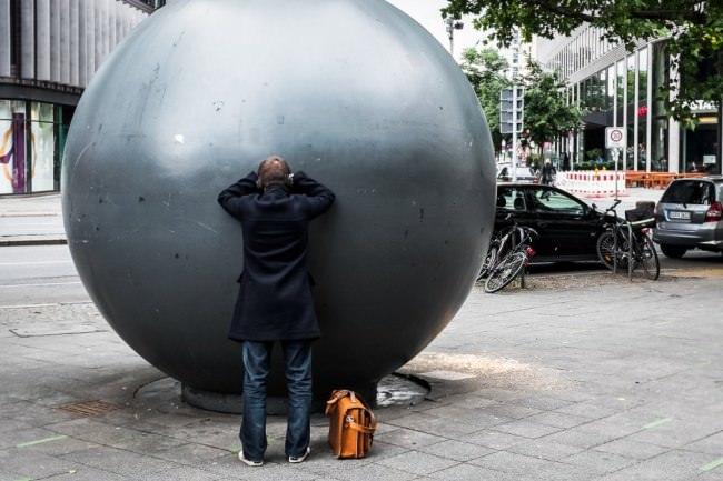 Ein Mensch schaut in eine große Kugel.