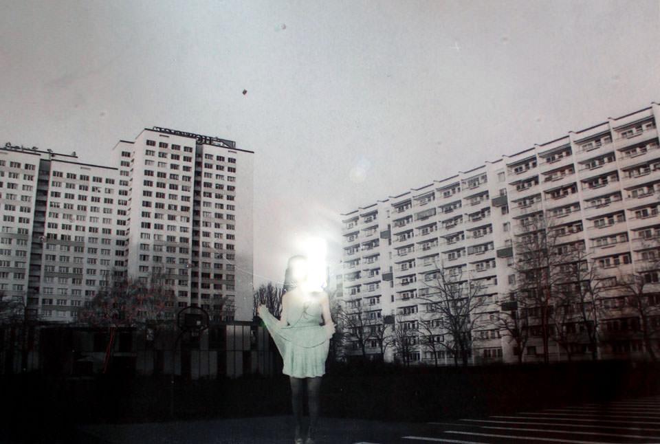 Eine Frau im Kleid vor Hochhäusern und Licht im Gesicht.
