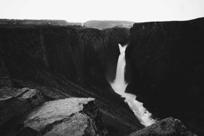 Schmaler Wasserfall zwischen schwarzen hohen Felsen.