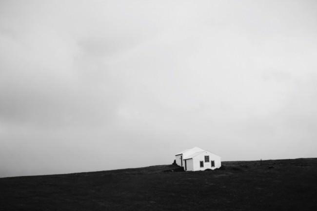 Ein weißes Häusschen auf schwarzem Strand.