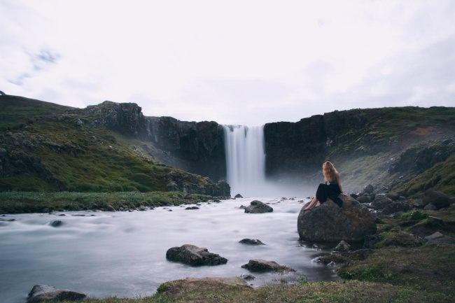 Frau sitzt auf einem Stein vor einem Wasserfall.