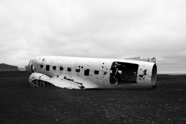 Flugzeugwrack im schwarzen Sand.