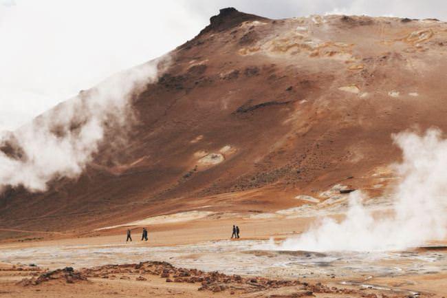 Wanderer vor einem Berg aus rotem Sand.