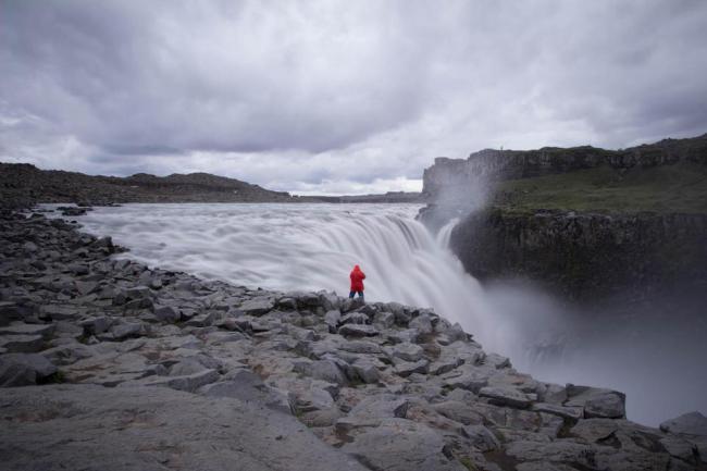 Mann mit roter Jacke vor einem Wasserfall.