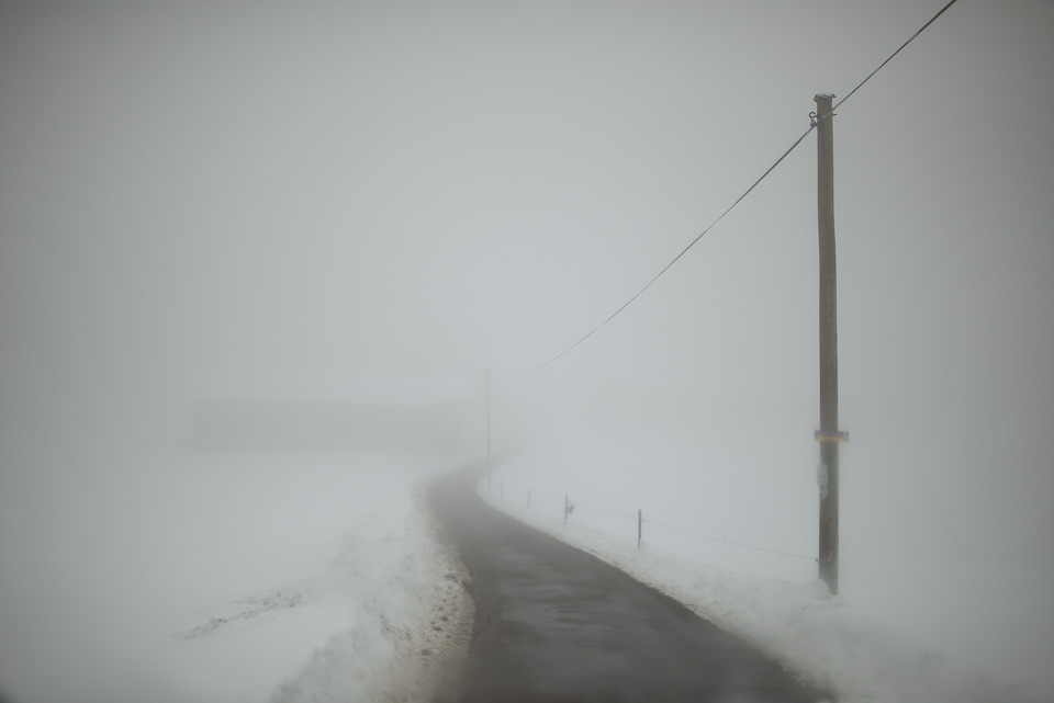 Strommast an einer Landstraße im Nebel.