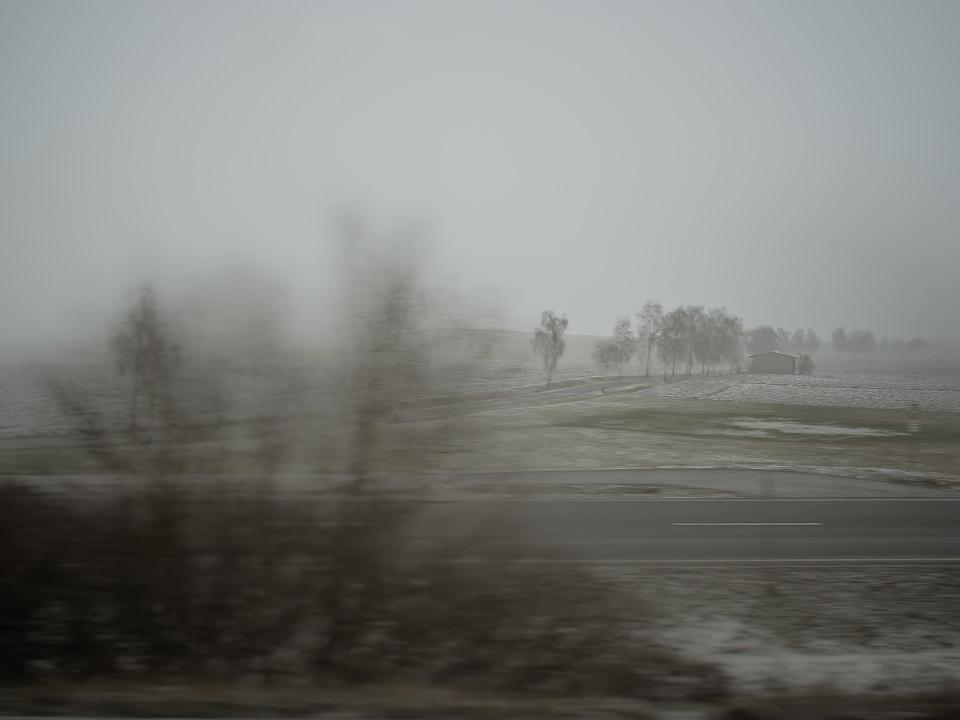 Verschneites Feld, beim Vorbeifahren fotografiert.