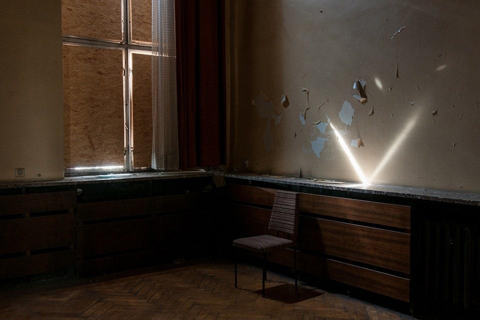 Ein Lichtstrahl fällt in einen verbarrikadierten Raum und spiegelt sich auf einer Platte an der Wand.