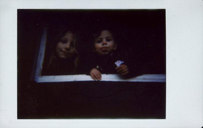 Zwei Kinder sehen aus einem Fenster