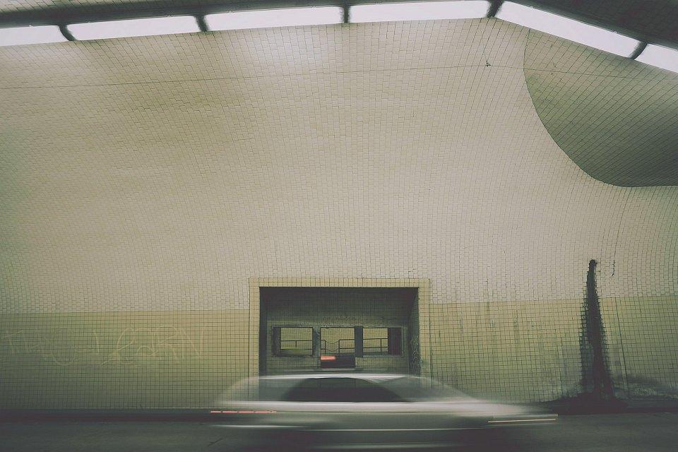 Vorbeifahrendes Auto in einem gefliesten Tunnel.