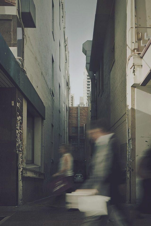Menschen gehen an einer Gasse zwischen hohen Häusern vorbei.