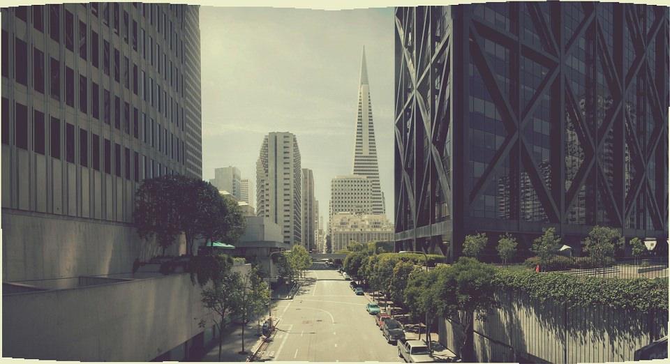 Breite Straße zwischen hohen Gebäuden, an deren Ende Hochhäuser stehen.