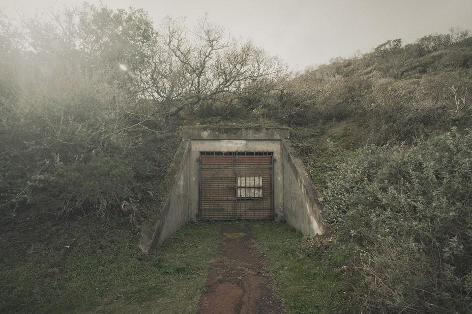 Eingang zu einer Bunkeranlage in einem Hügel in der Natur.