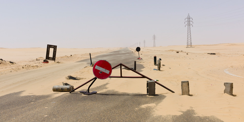 Absperrrung auf einer Straße durch die Wüste.