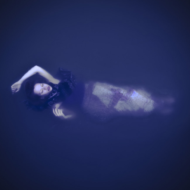 Frau liegt wie Meerjungfrau im Wasser
