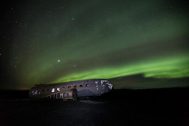 Flugzeugwrack bei Nacht. Polarlichter im Hintergrund.