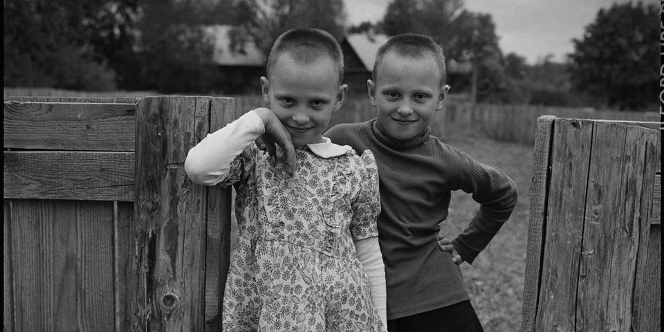 Zwei Kinder an einem Zaun