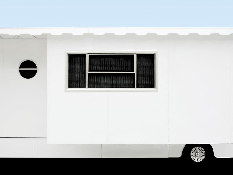 Seitenansicht eines weißen Schaustellerwagens.