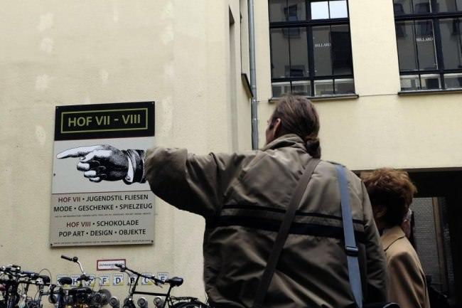 Straßenfotografie: Eine Hand an einer Wand sorgt für einen Bildwitz.