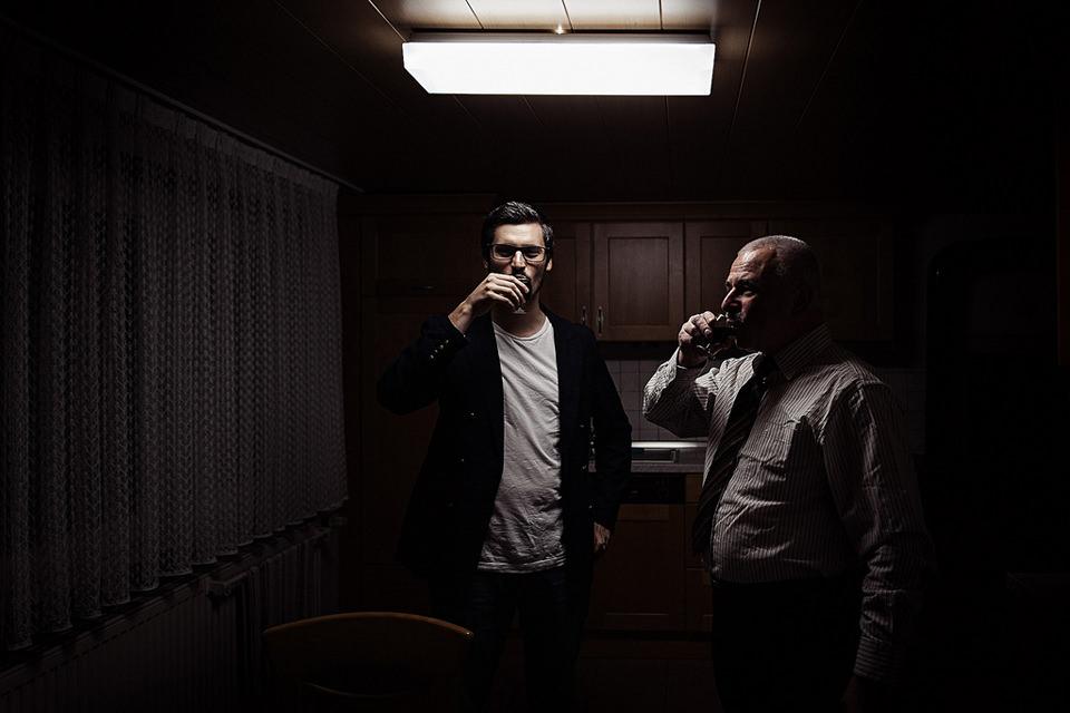 In der Küche stehen zwei Männer und trinken einen Schluck.