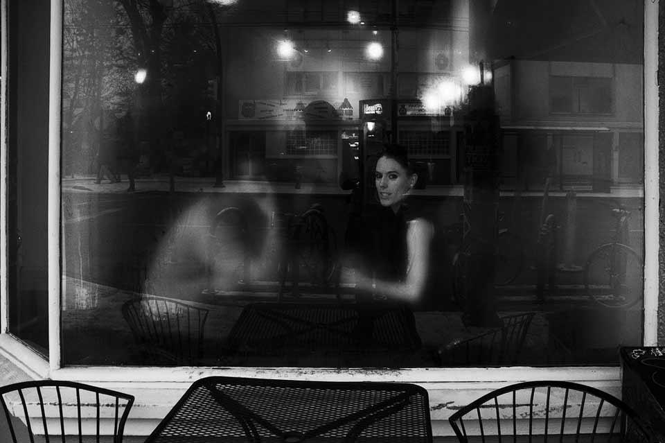Blick durch eine Scheibe auf ein Paar an einem Tisch im Cafe