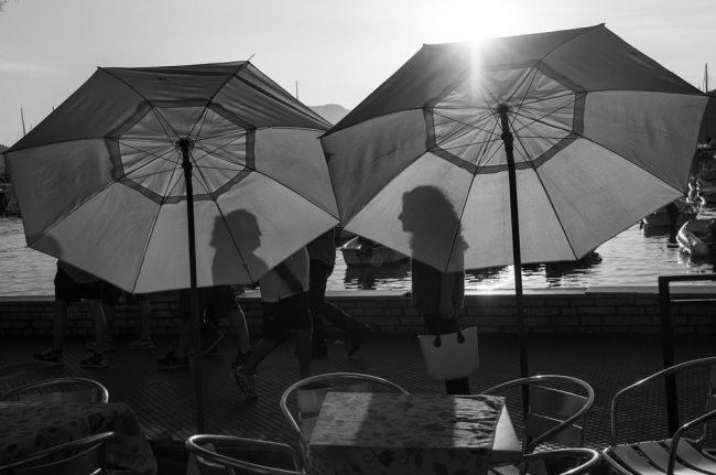 Zwei Frauen werfen Schatten auf zwei Schirme.