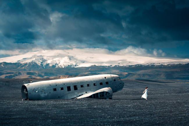 Eine Frau im weißen kleid läuft von einem Flugzeugwrack weg.
