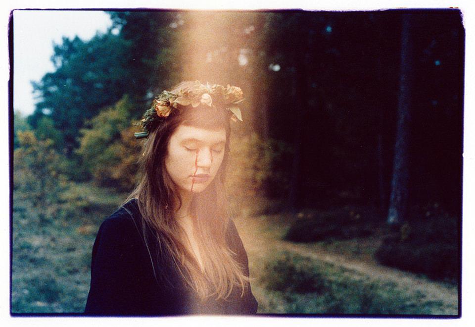 eine weinende Frau mit Blumenkranz