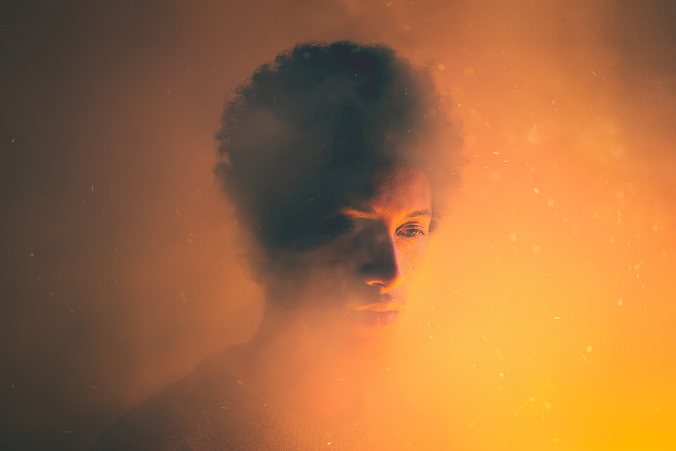 Portrait: Ein Mann wird von feuer-rotem Licht angeleuchtet.