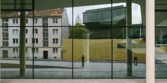 Ein Fotograf steht vor einem spiegelnden Gebäude und macht ein Foto.