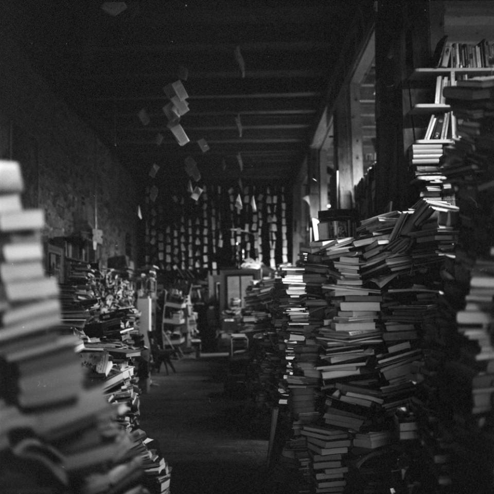 Blick in einen langen Raum voller Bücherstapel.