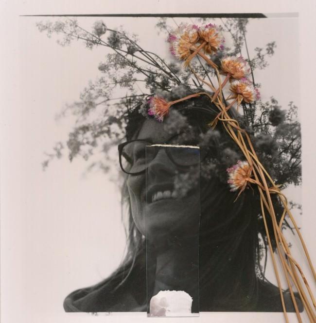 Schwarzweißtportrait eines Mädchens mit gescannter bunter Blume im Haar.