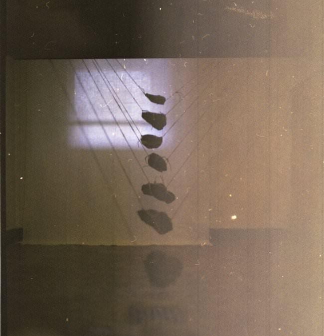 Steine an dünnen Fäden aufgehangen.