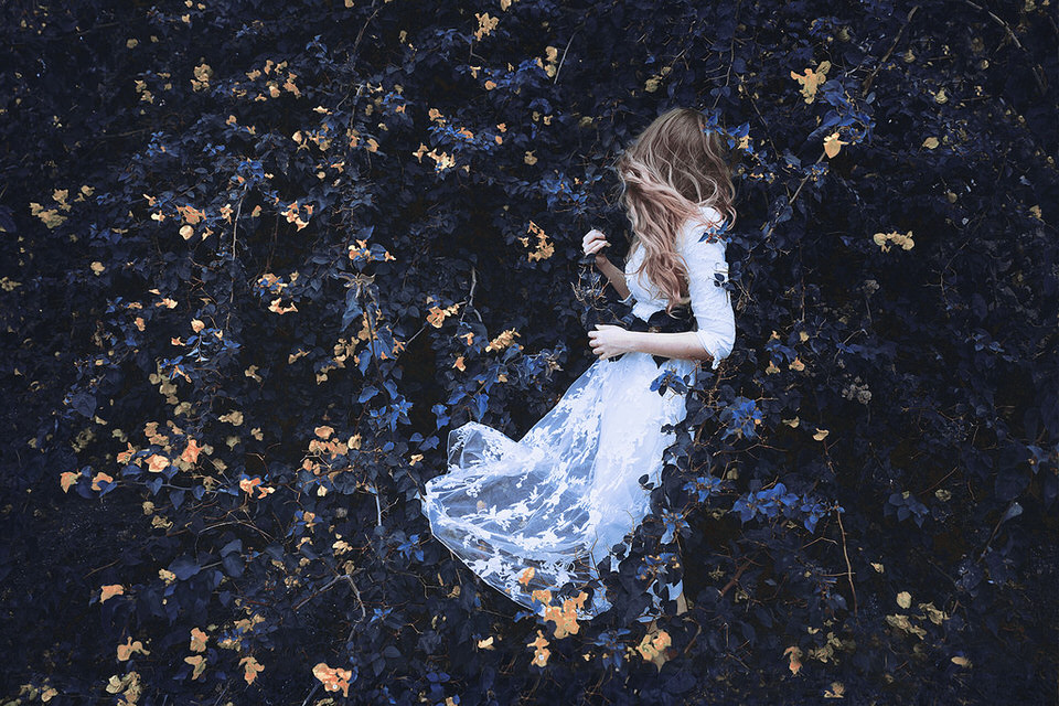 Frau in weißem Kleid zwischen blauen Blättern.