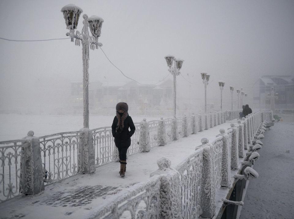 Eine Frau läuft über eine vereiste Brücke.